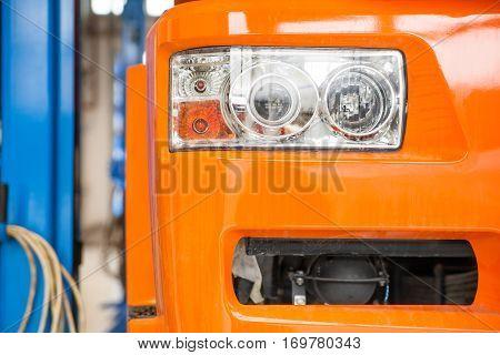 Focus on the big orange truck headlamp