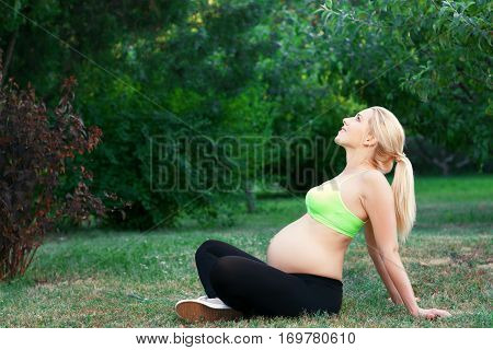 Pregnant woman having sunbath outdoor, free space. Side view of expectant blonde relaxing at nature, green environment background, copy space for text
