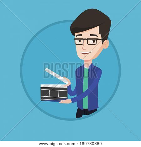 Happy smiling caucasian man holding an open clapperboard for the filming. Cheerful man holding blank movie clapperboard. Vector flat design illustration in the circle isolated on background.