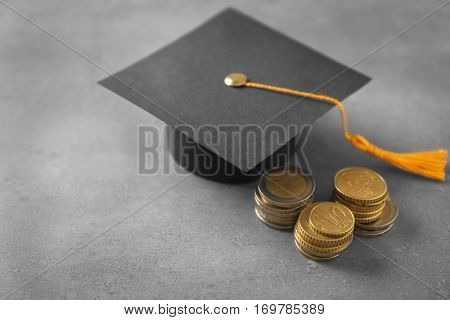 Graduation hat and coins on table. Pocket money concept