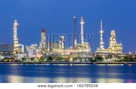 Scenic of oil refinery plant of Petrochemistry industry in twilight time and reflection in near river in Bangkok Thailand.