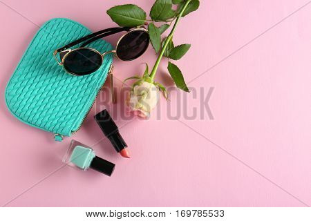 Cosmetic bag, rose and makeup products on color   background