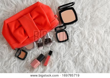 Cosmetic bag and makeup products on fur   background