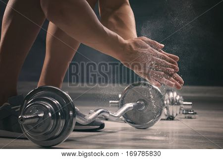 Sporty man applying talc powder onto hands prior to doing exercises with barbell, closeup