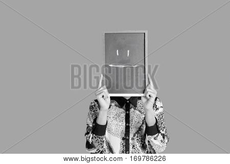 Teenage boy holding slate with blank expression smiley on it over red background