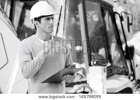 Thoughtful architect with clipboard and pen standing against earthmover at site