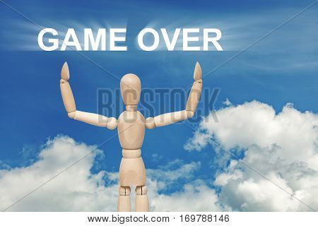 Wooden dummy puppet on sky background with words GAME OVER. Abstract conceptual image