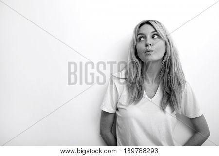 Thoughtful woman puckering against white background