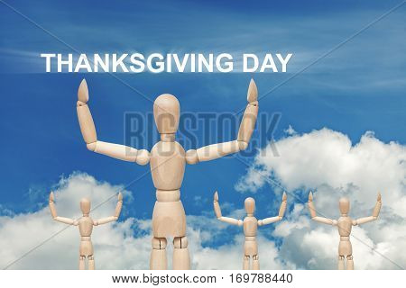 Wooden dummy puppet on sky background with words THANKSGIVING DAY. Abstract conceptual image