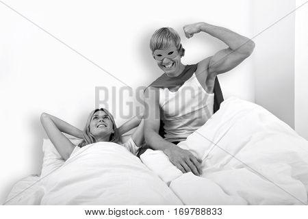 Portrait of man in superhero costume with woman on bed