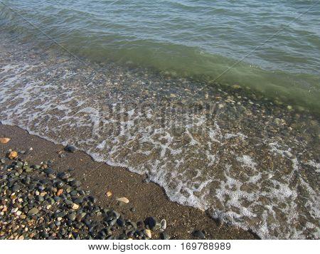 The sea wave runs on the desert stony coast