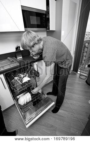 Full length of man loading dishwasher in kitchen