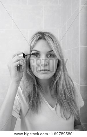 Portrait of young woman applying mascara in bathroom