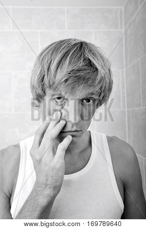 Portrait of sleepy man pulling eyelid in bathroom
