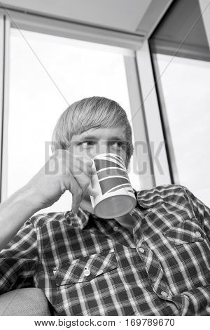 Thoughtful mid-adult man drinking coffee in living room at home