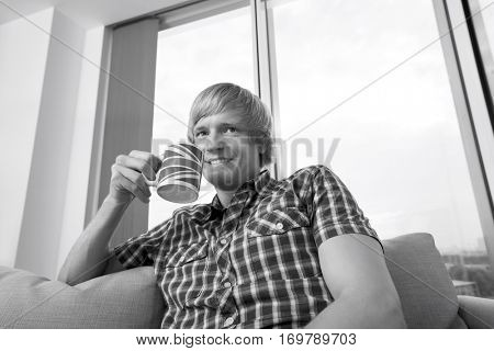 Thoughtful smiling mid-adult man with coffee cup in living room at home