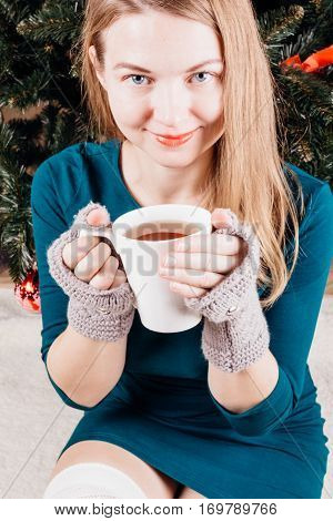 Beautiful girl with blonde hair in a green dress and fingerless gloves at the hands of holding a white cup with black tea on a background of a Christmas fir tree behind his back