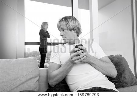 Mid-adult man text messaging while woman using cell phone in background at home