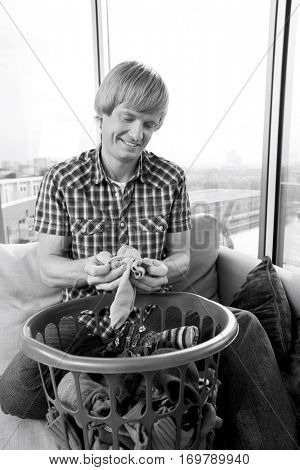 Smiling mid-adult man with laundry basket sitting on sofa at home