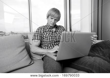 Serious mid-adult man using laptop on sofa at home