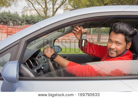 indian man sitting in the car showing car keys. concept of car rental, automobile business or vehicle ownership