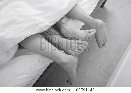 Low section of intimate couple in bed