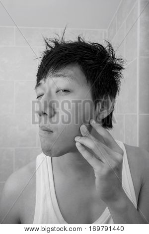 Asian mid adult man examining his face in bathroom
