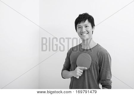 Portrait of happy mid adult man holding table tennis paddle