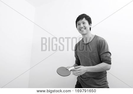 Handsome mid adult man holding table tennis paddle