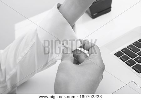 Cropped image of businessman buttoning his cuff in office