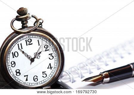 Fountain pen on spiral notebook near pocket watch with free space for text