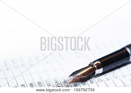 Closeup of fountain pen on paper background with digits