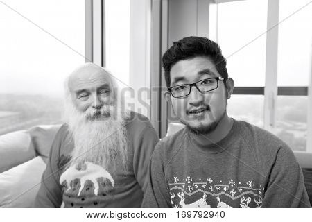 Portrait of young man with grandfather looking at him