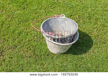 Two empty and dirty muddy bucket and red holder leave on the green grass garden background.