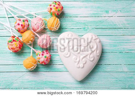 Bright cake pops and white heart on turquoise painted wooden background. Selective focus.
