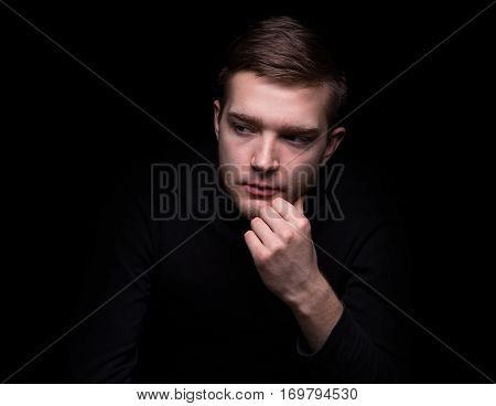 Portrait of attractive puzzled man on black background