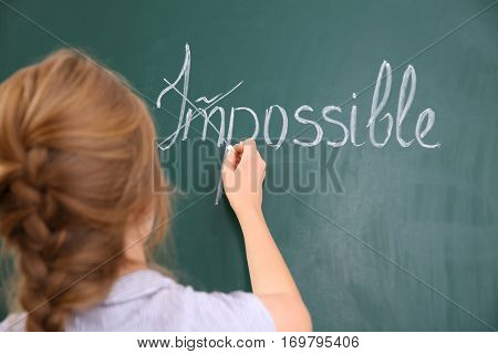 Woman transforming IMPOSSIBLE into POSSIBLE on chalkboard