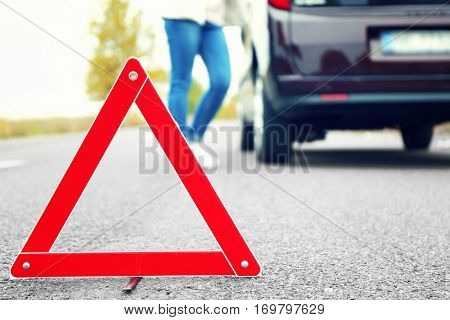 Traffic warning sign on road with car and female driver on background