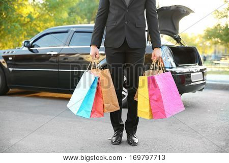 Chauffeur holding colourful packs and standing near luxury car, closeup