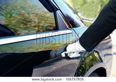 Closeup of chauffeur opening car door