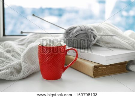 Cup of coffee, books and knitting on windowsill