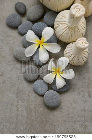 Pile of stone with frangipani,massage ball on grey background.