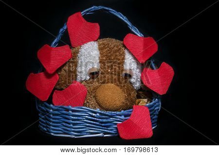 Handmaid busket with plushy dog and red origami hearts for Saint Valentine's Day on black background