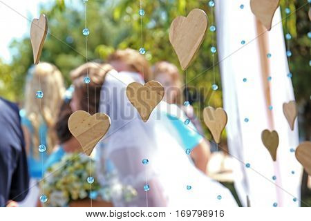 Wedding decor with wooden hearts and blurred newlyweds on background