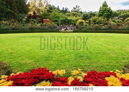 Picturesque ornamental park-garden Butchart Gardens on Vancouver Island, Canada. Green grass lawn and flower beds