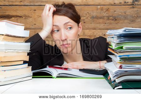 Woman got tired of working and studying next to the stack of papers and books. Work and study concept