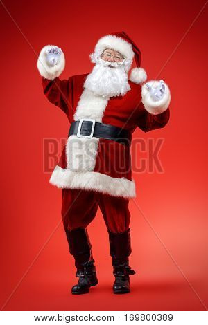 Full length portrait of a dancing Santa Claus over red background. Christmas and New Year concept.
