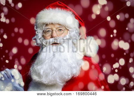 Santa Claus opened his eyes wide in surprise. Christmas Miracles. Portrait over red background.