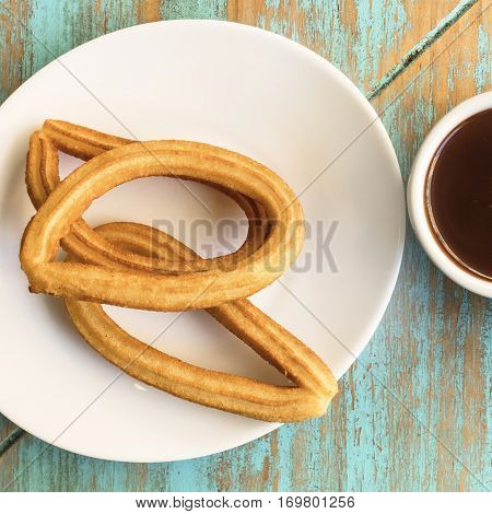 A square photo of a plate of churros, traditional Spanish, especially Madrid, dessert, particularly for Sunday breakfast, with a cup of hot chocolate, shot from above on a teal table with a place for text
