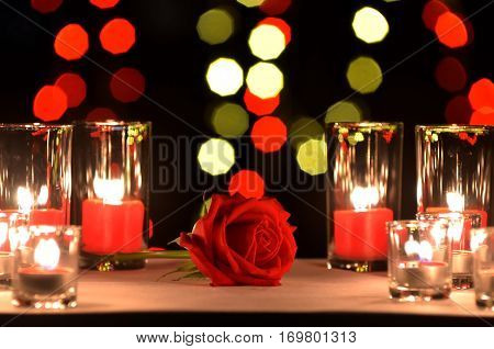 Beautiful red rose a concept of love and valentine's day put on a table with a candles in the glasses and blur enneagon yellow and red bokeh of light bulb in the backgroung in the night